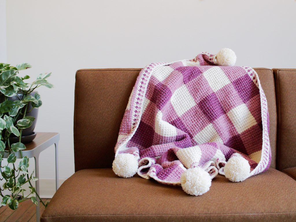 The Sweet Gingham Blanket was designed to bring rustic charm to your nursery. Simple stitching and colorwork techniques make this a fun and quick project, even for beginners who haven't tried Tunisian crochet yet. Play around with color to make a blanket that is perfect for your little angel. Pattern Highlights -Uses a lightweight worsted wool blend that is machine washable and soft on baby's sensitive skin. -This is the perfect pattern to learn Tunisian crochet! Follow along with helpful video tutorials, linked in this pattern. -Written pattern includes a schematic to help with color placement and details on adding the pom pom border.